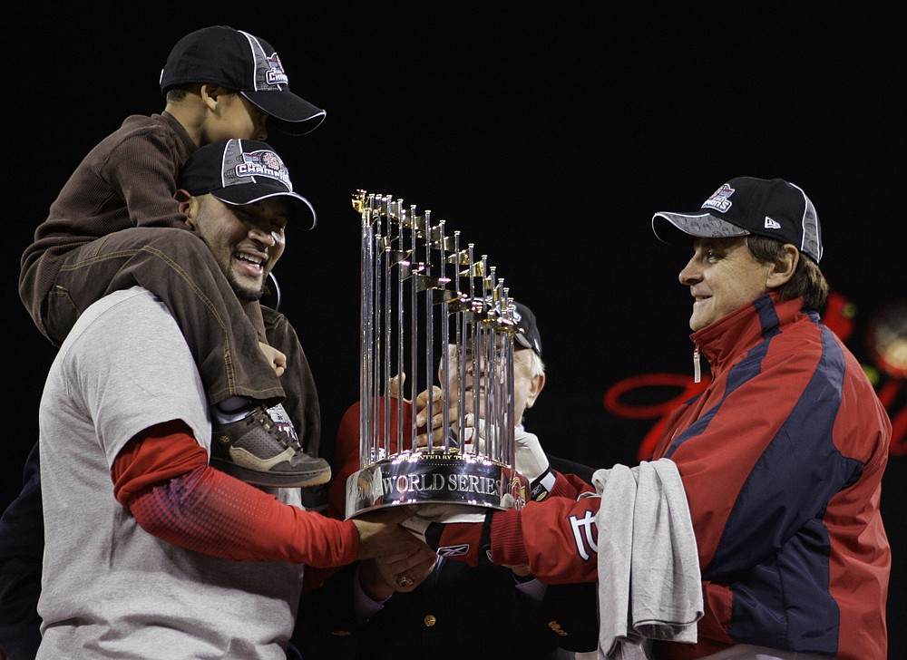 FILE - St. Louis Cardinals first baseman Albert Pujols, with his son A.J. Alberto Jr. on his shoulders, holds onto the World Series trophy with Cardinals manager Tony La Russa, right and General Manager Walt Jocketty, second right, after winning Game 5 of the World Series against the Detroit Tigers in St. Louis, in this Friday, Oct. 27, 2006, file photo. Pujols has been designated for assignment by the Los Angeles Angels, abruptly ending the 41-year-old superstar slugger's decade with his second major league team. The Angels announced the move Thursday, May 6, 2021, a day after Pujols wasn't in their lineup for their fourth consecutive loss.  (AP Photo/Elise Amendola, File)