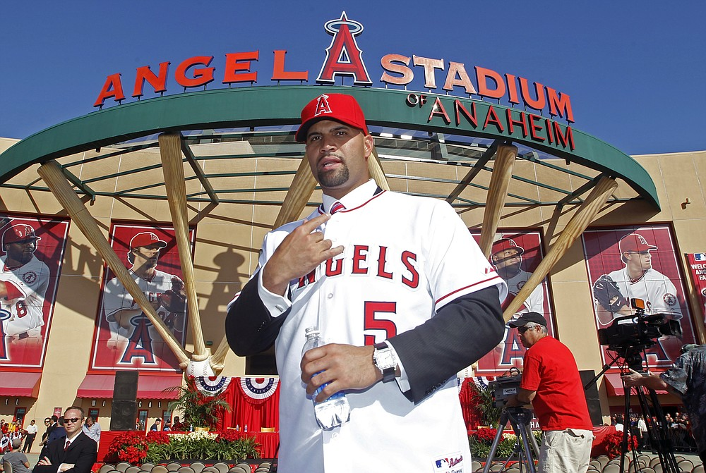 FILE - In this Dec. 10, 2011, file photo, Los Angeles Angels' Albert Pujols wears his new jersey after a news conference to introduce Pujols and C.J. Wilson (not pictured) as the newest Angels baseball players in Anaheim, Calif. Pujols has been designated for assignment by the Los Angeles Angels, abruptly ending the 41-year-old superstar slugger's decade with his second major league team. The Angels announced the move Thursday, May 6, 2021, a day after Pujols wasn't in their lineup for their fourth consecutive loss. (AP Photo/Alex Gallardo, File)
