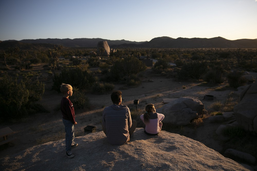 FILE - In this May 19, 2020, file photo Aaron Stubbs and his two children sit on a rock to watch sunset at Joshua Tree National Park in California. The Biden administration is outlining a plan to sharply increase conservation of public lands and waters over the next decade. A report to be issued Thursday recommends a series of steps to achieve a nationwide goal to conserve 30% of U.S. lands and waters by 2030. (AP Photo/Jae C. Hong, File)