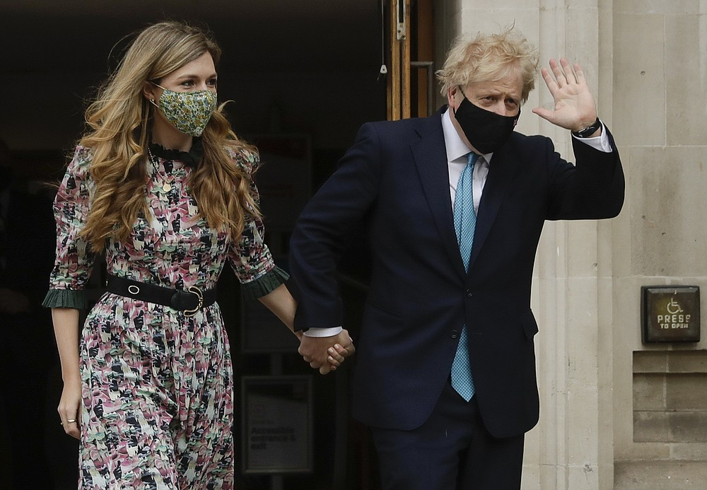British Prime Minister Boris Johnson waves as he leaves a polling station with his partner Carrie Symonds after casting his vote in local council elections in London, Thursday May 6, 2021. Millions of people across Britain will cast a ballot on Thursday, in local elections, the biggest set of votes since the 2019 general election. A Westminster special-election is also taking place in Hartlepool, England. (AP Photo/Matt Dunham)