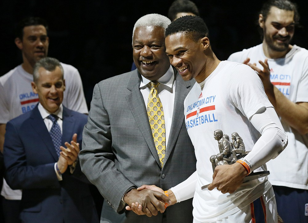 FILE - Then-Oklahoma City Thunder guard Russell Westbrook, right, is congratulated by Oscar Robertson on his single season triple-double record before an NBA basketball game between the Denver Nuggets and the Oklahoma City Thunder in Oklahoma City, Okla., in this Wednesday, April 12, 2017, file photo. Westbrook's stat lines have been looking like typos in the box score lately, and now he's on the verge of something historic. The Washington Wizards point guard's next triple-double – which could come as soon as Saturday, May 8, 2021, will be the 181st of his career, tying Oscar Robertson's NBA record. (AP Photo/Sue Ogrocki, File)