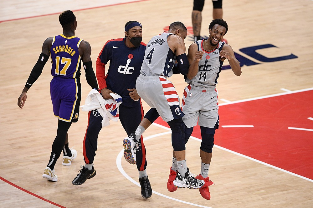 Washington Wizards guard Ish Smith (14) celebrates after his dunk with guard Russell Westbrook (4) and guard Bradley Beal, second from left, during the second half of an NBA basketball game as Los Angeles Lakers guard Dennis Schroder (17) walks by, Wednesday, April 28, 2021, in Washington. (AP Photo/Nick Wass)