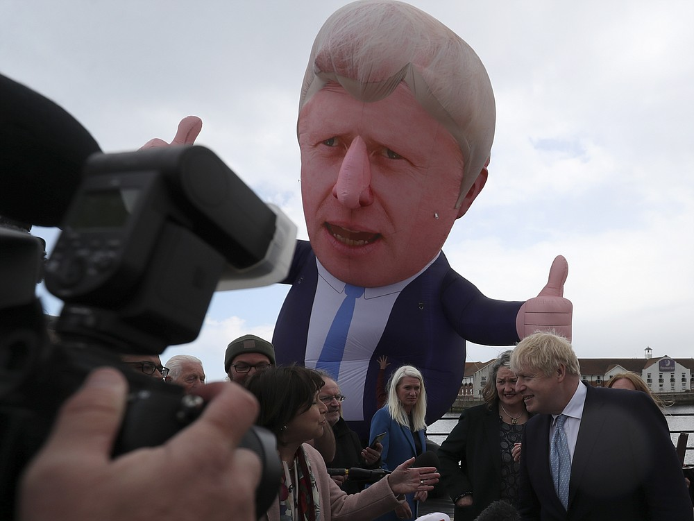 British Prime Minister Boris Johnson speaks to the media next to a large inflatable of him and flanked by Jill Mortimer, the winning Conservative Party candidate of the Hartlepool by-election, at Hartlepool Marina, in Hartlepool, north east England, Friday, May 7, 2021. Britain's governing Conservative Party made further inroads in the north of England on Friday, winning a by-election in the post-industrial town of Hartlepool for a parliamentary seat that the main opposition Labour Party had held since its creation in 1974. (AP Photo/Scott Heppell)