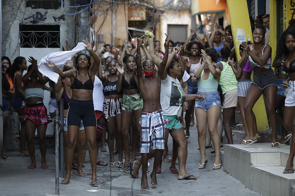 EDS NOTE: OBSCENITY - Youths protest a police operation targeting drug traffickers in the Jacarezinho favela of Rio de Janeiro, Brazil, Thursday, May 6, 2021. At least 25 people died during the operation, including one police officer and 24 suspects, according to the press office of Rio's civil police. (AP Photo/Silvia Izquierdo)