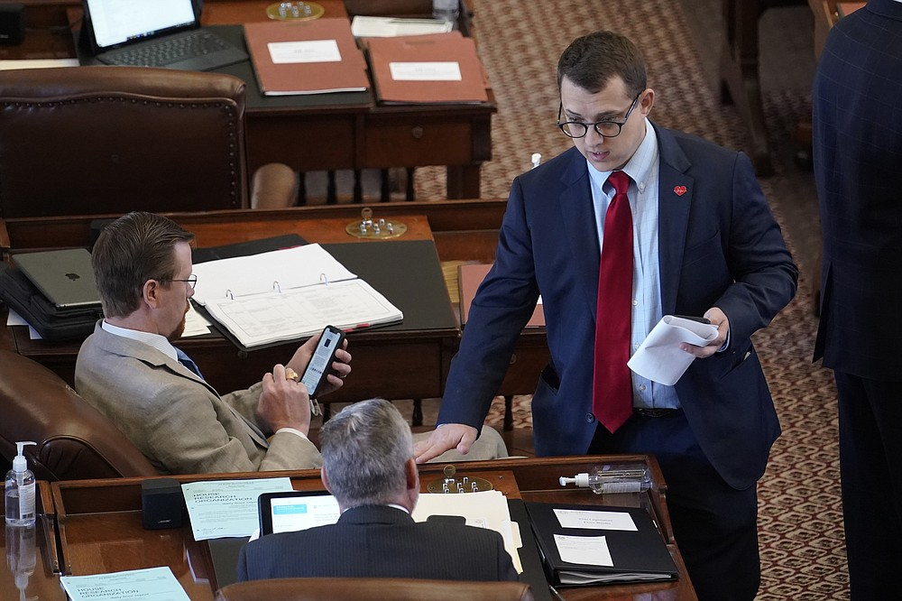 State Rep. Briscoe Cain, R-Houston, right, talks with fellow lawmakers in the House Chamber at the Texas Capitol as they wait to hear debate on voter legislation, Thursday, May 6, 2021, in Austin, Texas. (AP Photo/Eric Gay)
