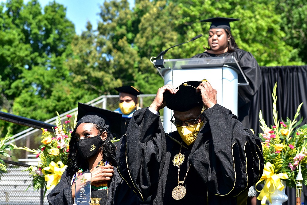 UAPB Chancellor Laurence B. Alexander fixes his doctoral tam as Chancellor's Medallion winner Courtnei D. Toney, left, of Memphis is recognized and registrar Jeanese Outlaw announces the winners during spring commencement Saturday, May 8, 2021. (Pine Bluff Commercial/I.C. Murrell)