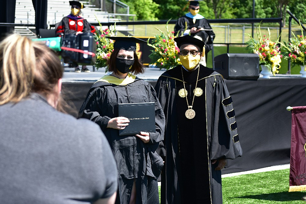 A UAPB agriculture student poses with UAPB Chancellor Laurence B. Alexander for a photo upon receiving her degree Saturday, May 8, 2021, at Simmons Bank Field. (Pine Bluff Commercial/I.C. Murrell)