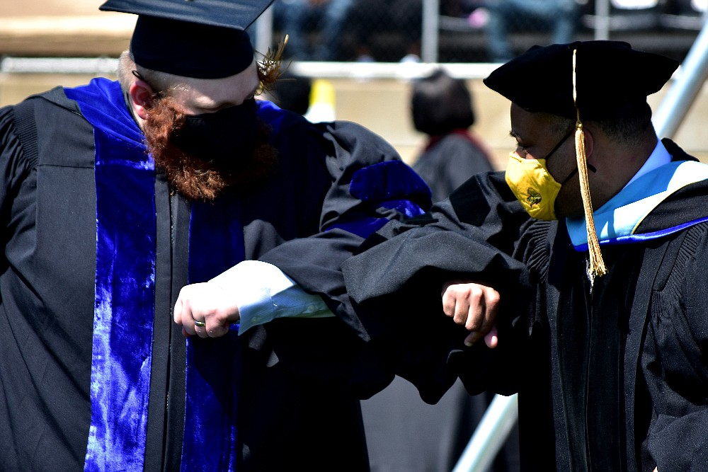 Jeremiah Salinger, left, bumps elbows with a UAPB faculty member as he receives his doctorate in philosophy Saturday, May 8, 2021, at Simmons Bank Field. (Pine Bluff Commercial/I.C. Murrell)
