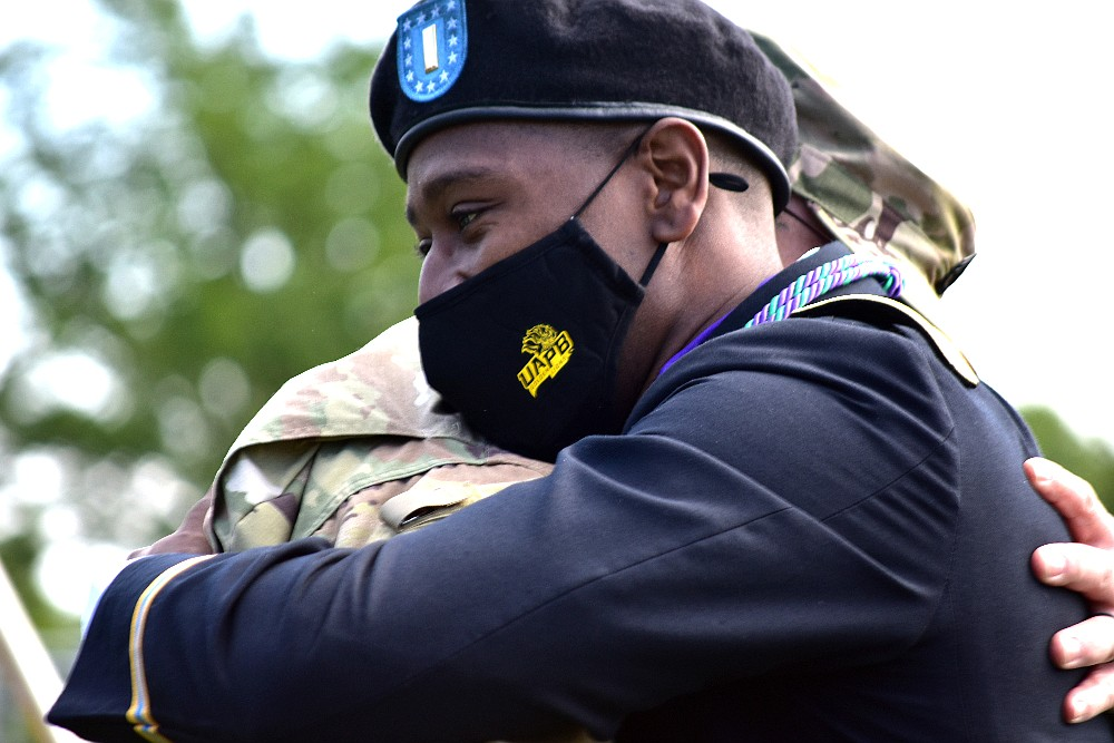 A newly commissioned U.S. Army officer, foreground, embraces a Reserve Officers' Training Corps faculty member after a ceremonial salute during UAPB spring commencement Saturday, May 8, 2021, at Simmons Bank Stadium. (Pine Bluff Commercial/I.C. Murrell)