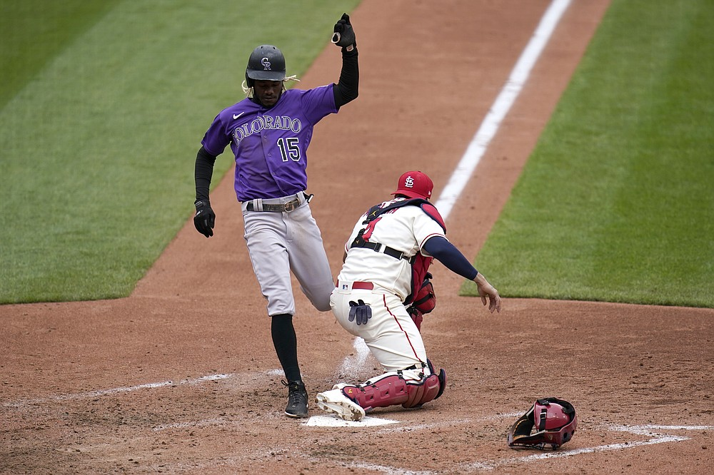 Colorado Rockies' Raimel Tapia (15) is forced out as St. Louis Cardinals catcher Yadier Molina covers home during the fifth inning of a baseball game Saturday, May 8, 2021, in St. Louis. (AP Photo/Jeff Roberson)