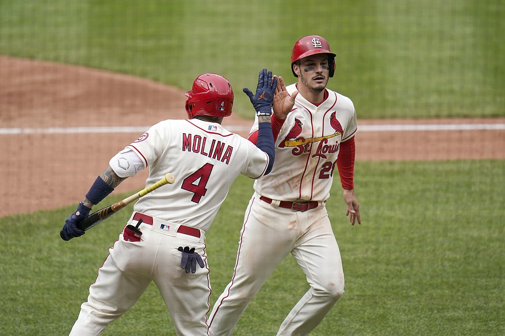 St. Louis Cardinals' Nolan Arenado, right, is congratulated by teammate Yadier Molina (4) after scoring during the fifth inning of a baseball game against the Colorado Rockies Saturday, May 8, 2021, in St. Louis. (AP Photo/Jeff Roberson)