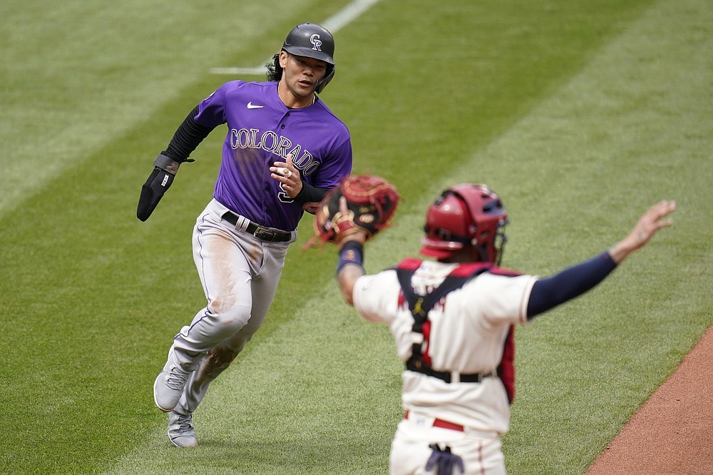 Colorado Rockies' Connor Joe, left, scores past St. Louis Cardinals catcher Yadier Molina on a three-run double by Dom Nunez during the fifth inning of a baseball game Saturday, May 8, 2021, in St. Louis. (AP Photo/Jeff Roberson)