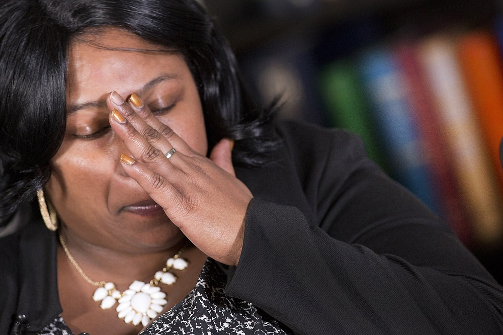 FILE - In this Dec, 15, 2014 file photo, Samaria Rice, of Cleveland, Ohio, mother of Tamir Rice, touches her hand to her face during an interview at The Associated Press, in New York. A Cleveland police officer fatally shot 12-year-old Tamir Rice on Nov. 22 as he played with a toy gun outside a recreation center. The family of 12-year-old Tamir Rice, who was shot and killed by Cleveland police in 2014, asked the Justice Department on Friday to reopen the case into the boy's death after it was closed in the waning weeks of the Trump administration. (AP Photo/Mark Lennihan)