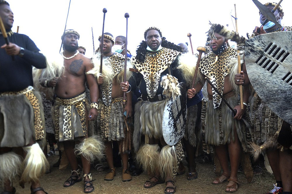 """Prince Misuzulu Zulu, centre, flanked by fellow warriors in traditional dress at the KwaKhangelamankengane Royal Palace, during a ceremony, in Nongoma, Friday May 7, 2021. A new Zulu king in South Africa has been named amid scenes of chaos as other members of the royal family questioned Prince Misuzulu Zulu's claim to the title. He was suddenly whisked away from the public announcement at a palace by bodyguards. The controversy over the next king has arisen after the death in March of King Goodwill Zwelithini, who had reigned since 1968. Zwelithini apparently named one of his six wives, Queen Mantfombi Shiyiwe Dlamini Zulu, as the """"regent of the Zulu kingdom"""" in his will. But her death just over a week ago after holding the title for only a month has thrown the royal succession into turmoil. (AP Photo)"""