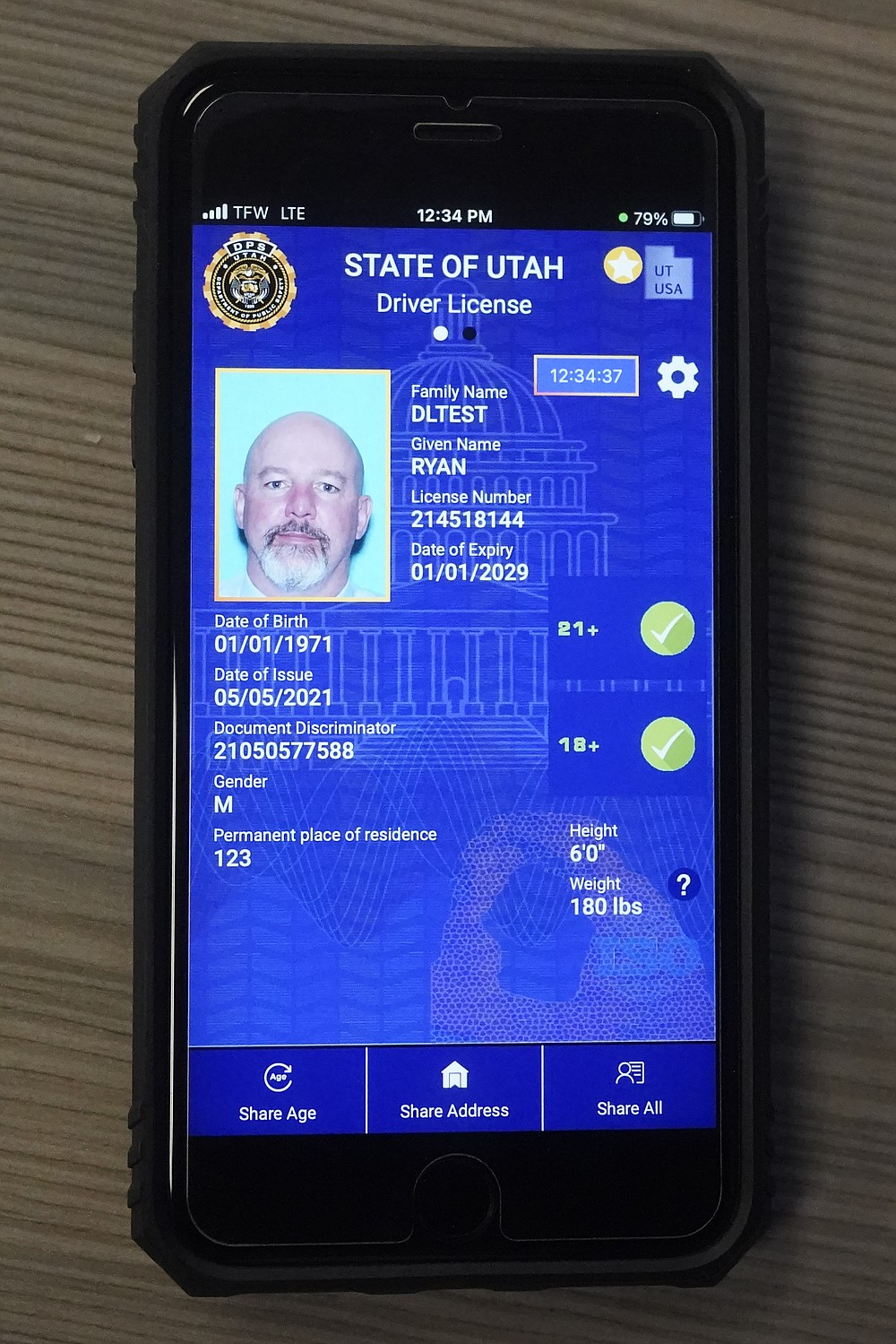 A cell phone with the pilot version of the Utah's mobile ID is shown on Wednesday, May 5, 2021, in West Valley City, Utah. The card that millions of people use to prove their identity to everyone from police officers to liquor store owners may soon be a thing of the past as a growing number of states develop digital driver's licenses. In Utah, over 100 people have a pilot version of the state's mobile ID, and that number is expected to grow to 10,000 by year's end. Widespread production is expected to begin at the start of 2022. (AP Photo/Rick Bowmer)