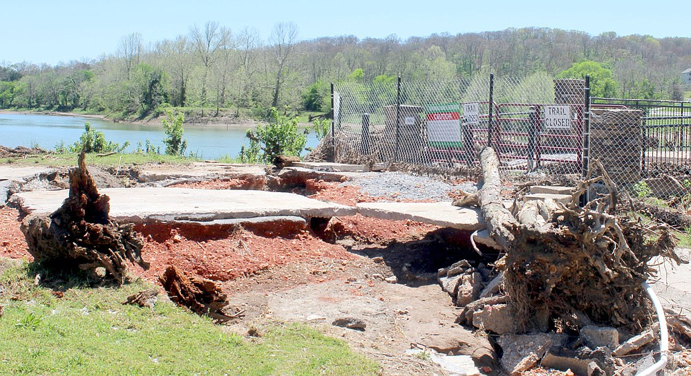 Keith Bryant/The Weekly Vista A great deal of concrete is undercut and washed out while massive objects, including a tree snag, remain after being onto the former entryway for the Lake Bella Vista Dam during a late April rainstorm.