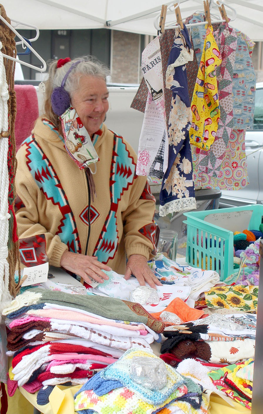 Keith Bryant/The Weekly Vista Becky Hedden with Posy Mountain Plantation, sorts some of her fabric goods during a lull in business at last Sunday's Bella Vista Farmers Market.