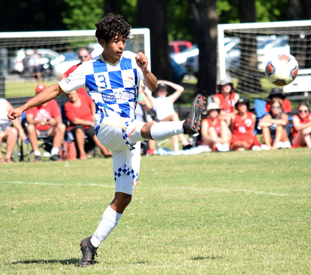 Westside Eagle Observer/MIIKE ECKELS  Bryan Ruiz kicks the ball toward a team mate during the second round of the 3A state playoff match between the Harding Academy Wildcats and the Decatur Bulldogs Friday afternoon in North Little Rock. The Wildcats ended the Bulldogs 2021 season 7-0.