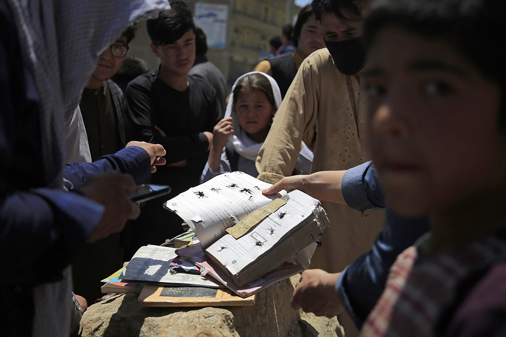 Afghans go through belongings left behind after deadly bombings on Saturday near a school in Kabul, Afghanistan, Sunday, May 9, 2021. The Interior Ministry said the death toll in the horrific bombing at the entrance to a girls' school in the Afghan capital has soared to some 50 people, many of them pupils between 11 and 15 years old, and the number of wounded in Saturday's attack has also climbed to more than 100. (AP Photo/Mariam Zuhaib)