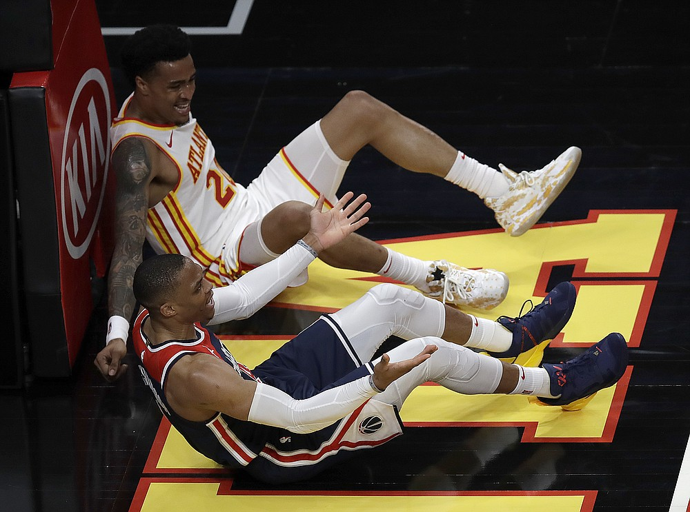 Washington Wizards' Russell Westbrook, foreground, reacts beside Atlanta Hawks' John Collins on the floor in the second half of an NBA basketball game Monday, May 10, 2021, in Atlanta. (AP Photo/Ben Margot)