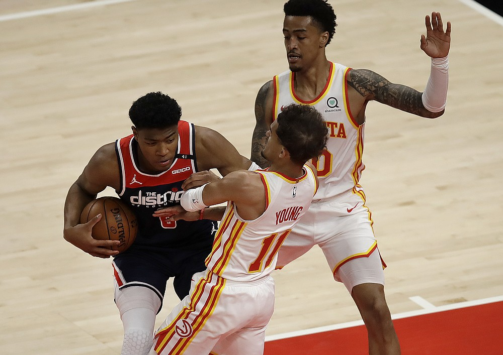 Washington Wizards' Rui Hachimura, left, drives the ball against Atlanta Hawks' Trae Young (11) in the first half of an NBA basketball game Monday, May 10, 2021, in Atlanta. (AP Photo/Ben Margot)