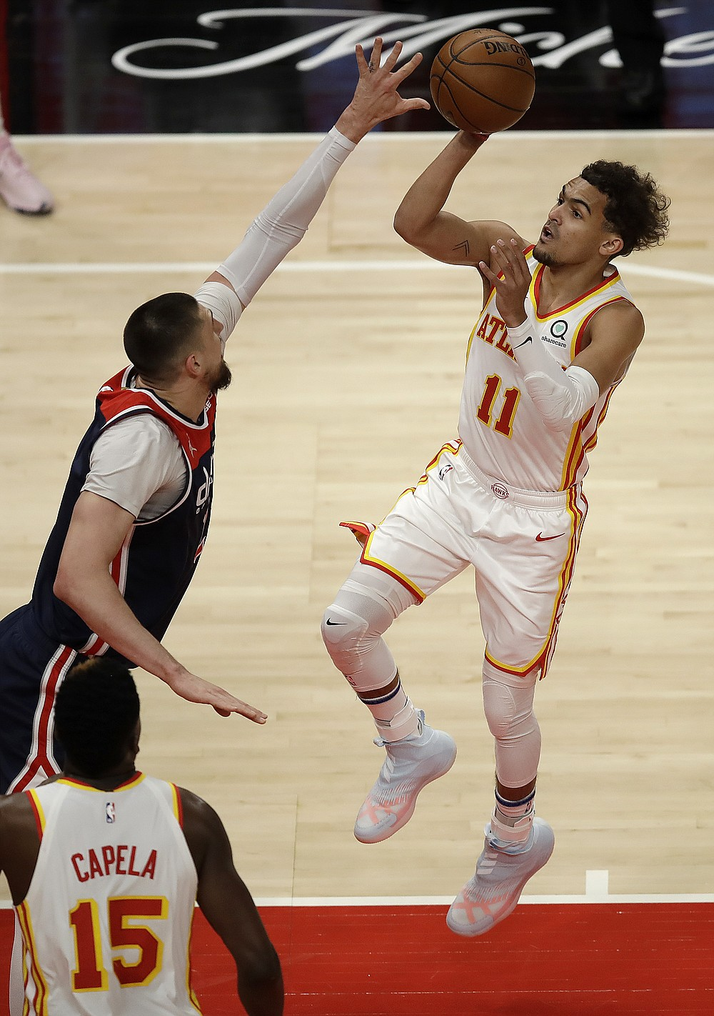 Atlanta Hawks' Trae Young, right, shoots over Washington Wizards' Alex Len during the first half of an NBA basketball game Monday, May 10, 2021, in Atlanta. (AP Photo/Ben Margot)