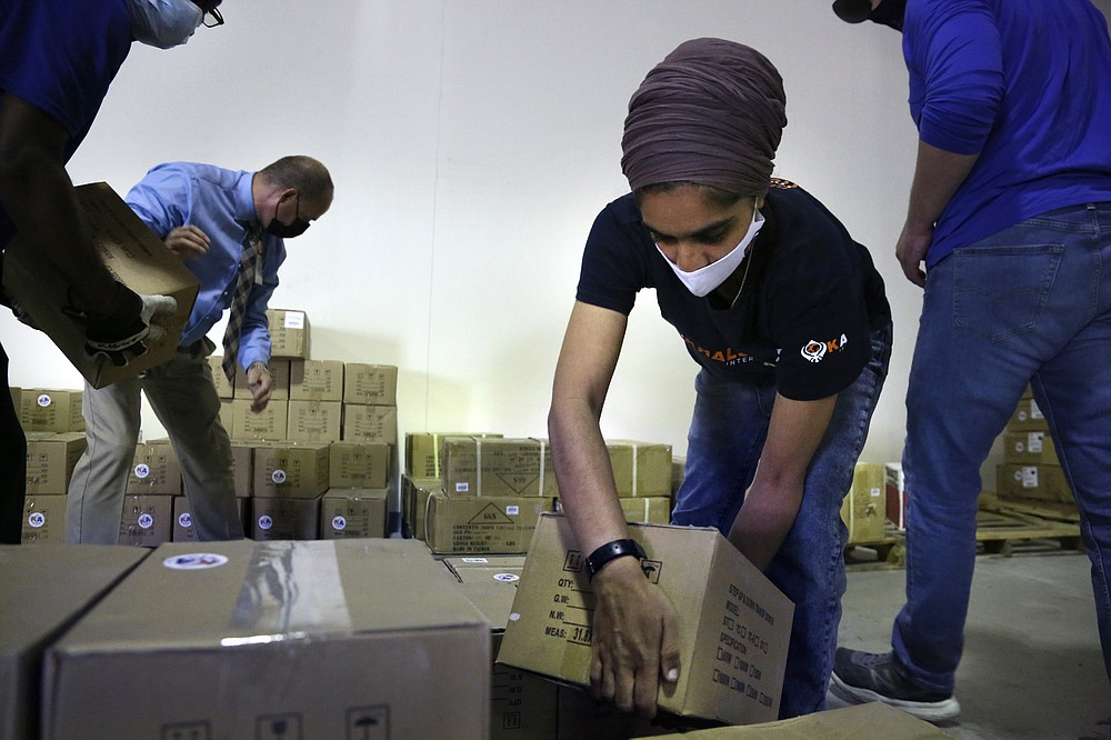 From left, Tim Williams, warehouse assistant for Medisys, Ray Fredericks, assistant director for Medisys, Dr. Abhu Kaur with Khalsa Aid USA, a global humanitarian organization, and Michael Stack, healthcare account representative for Grainger, load dozens of electrical transformers onto a pallet, which will be shipped to New Delhi with oxygen concentrators this week on New York's Long Island, Friday, May 7, 2021. With teams deployed in India to help support COVID-19 patients, Khalsa Aid USA plans to provide a total of 500 oxygen concentrators and 500 transformers to cities throughout the country. (AP Photo/Jessie Wardarski)