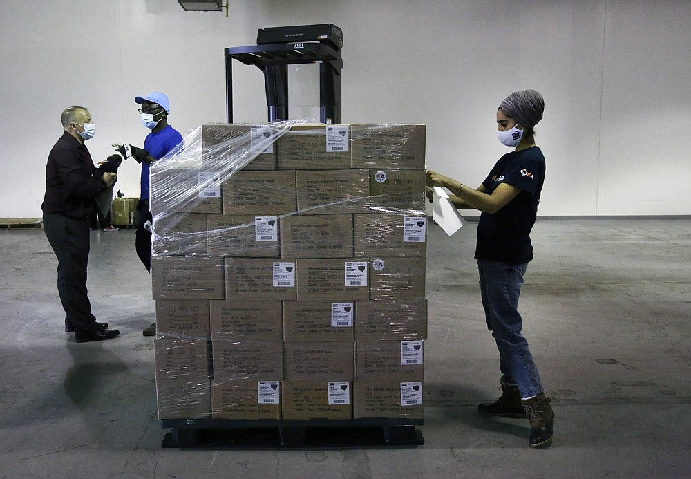 Dr. Abhu Kaur of Khalsa Aid USA, a global humanitarian organization, labels a pallet of electrical transformers, which will be shipped to New Delhi with oxygen concentrators this week, on New York's Long Island, Friday, May 7, 2021. With teams deployed in India to help support COVID-19 patients, Khalsa Aid USA plans to provide a total of 500 oxygen concentrators and 500 transformers to cities throughout the country. (AP Photo/Jessie Wardarski)