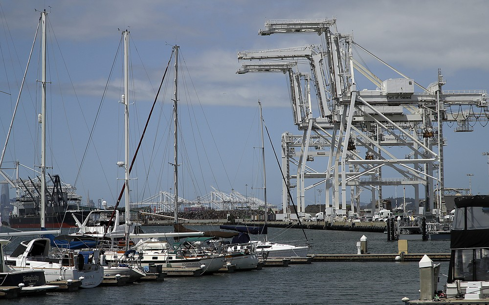 FILE - In this photo taken on Friday, May 17, 2019, shipping cranes and a marina are seen near the Howard terminal area of the Port of Oakland in Oakland, Calif. Major League Baseball instructed the Athletics to explore relocation options as the team tries to secure a new ballpark it hopes will keep the club in Oakland in the long term. A's owner John Fisher said in a statement he will honor MLB's instructions but remains committed to continuing to pursue the waterfront ballpark proposed for construction in the city's Howard Terminal location, close to the popular Jack London Square neighborhood. (AP Photo/Ben Margot, File)