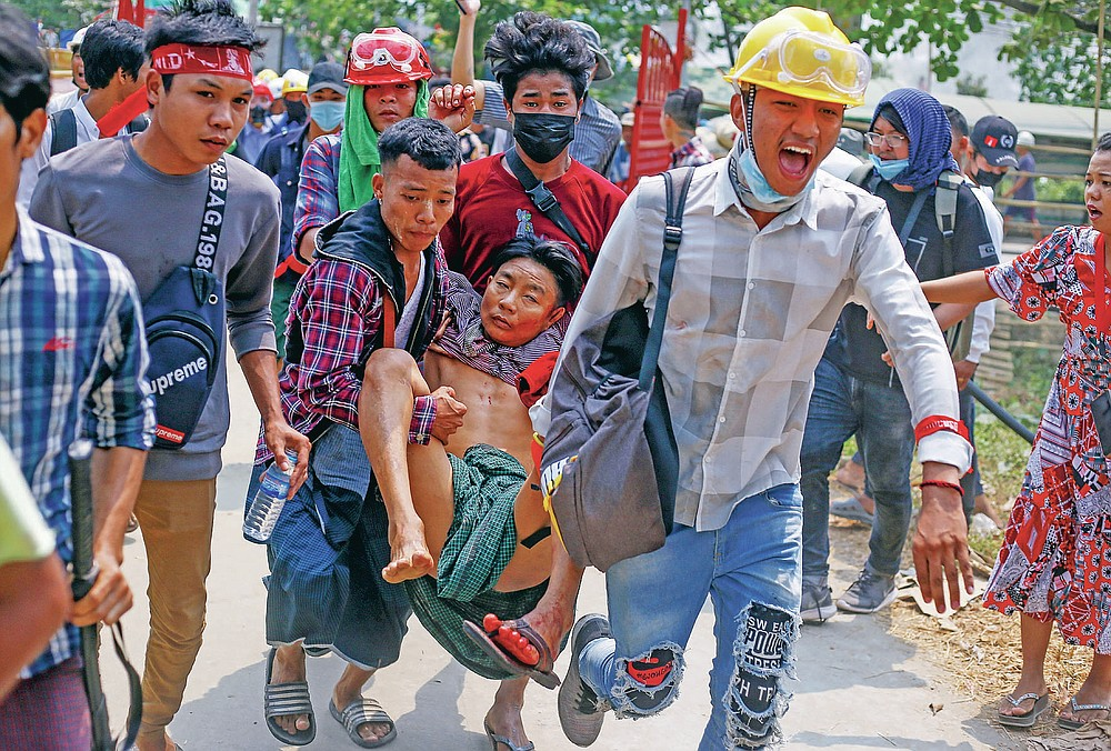 FILE - In this March 14, 2021, file photo, anti-coup protesters carry an injured man following clashes with security in Yangon, Myanmar. The military takeover of Myanmar early in the morning of Feb. 1 reversed the country's slow climb toward democracy after five decades of army rule. But Myanmar's citizens were not shy about demanding their democracy be restored. (AP Photo, File)