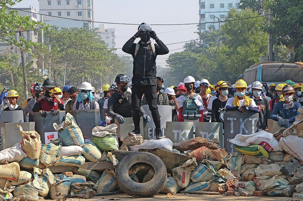 FILE - In this March 7, 2021, file photo, protesters take positions behind a barricades as police gather in Yangon, Myanmar. The military takeover of Myanmar early in the morning of Feb. 1 reversed the country's slow climb toward democracy after five decades of army rule. But Myanmar's citizens were not shy about demanding their democracy be restored. (AP Photo, File)