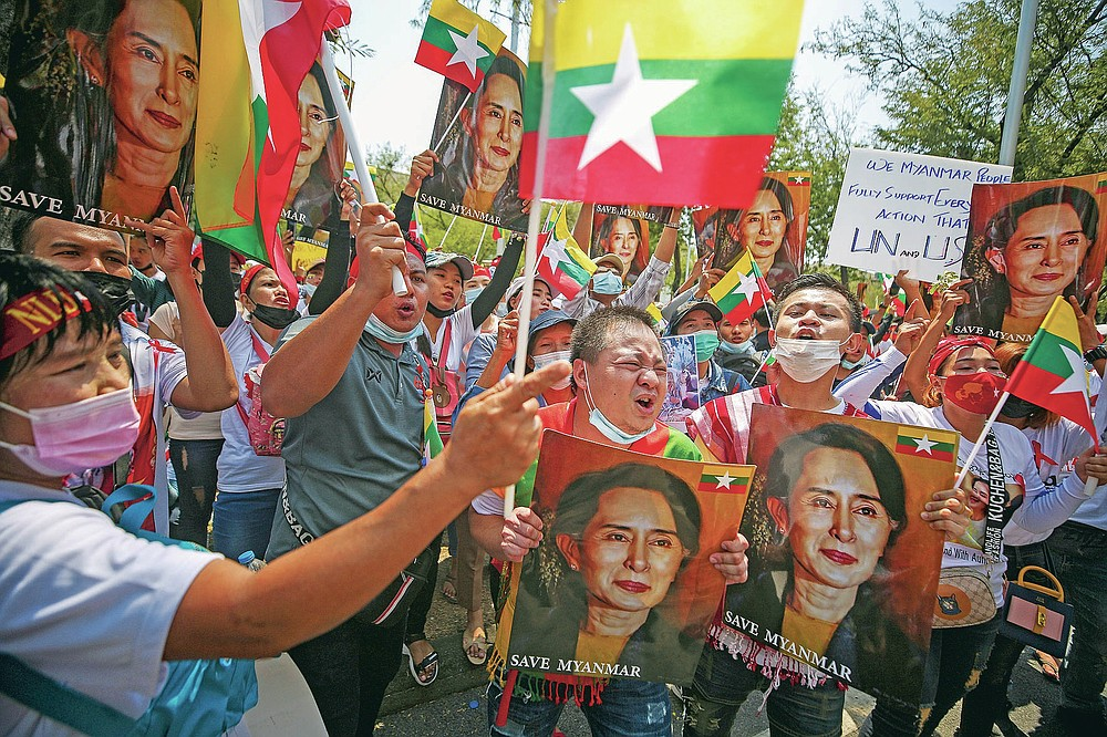 FILE - In this March 7, 2021, file photo, Myanmar nationals living in Thailand hold pictures of deposed Myanmar leader Aung San Suu Kyi as they protest against the military coup in front of the United Nations building in Bangkok, Thailand. The military takeover of Myanmar early in the morning of Feb. 1 reversed the country's slow climb toward democracy after five decades of army rule. But Myanmar's citizens were not shy about demanding their democracy be restored. (AP Photo/Nava Sangthong, File)