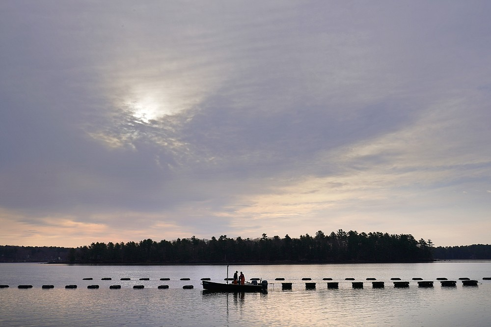 Oyster farmers Sam Dorval and Chris Burtis of Ferda Farms harvest oysters from floating crates on the New Meadows River, Sunday, April 25, 2021, in Brunswick, Maine. Oysters from the farm are being used to support an existing population in New Hampshire's Great Bay. (AP Photo/Robert F. Bukaty)