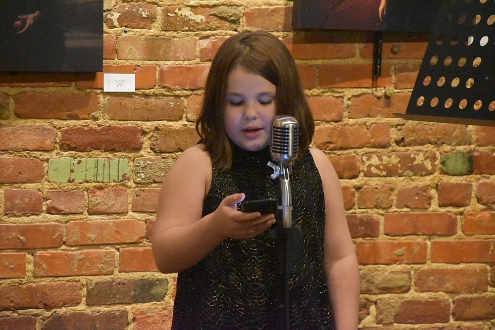 Veda Gonzales, 9, the youngest poet ever featured at the Wednesday Night Poetry reading, delivers a pre-covid performance at Kollective Coffee+Tea in Hot Springs. (Courtesy of Wednesday Night Poetry)