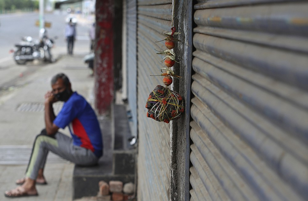 Lemon and chillies, believed to ward away the evil are hung outside a closed shop during restrictions to curb the spread of coronavirus in Jammu, India, Wednesday, May 12, 2021. Misinformation about the coronavirus is surging in India as the death toll from COVID-19 rises. Fueled by anguish, distrust and political polarization, the claims are further compounding India's crisis. (AP Photo/Channi Anand)
