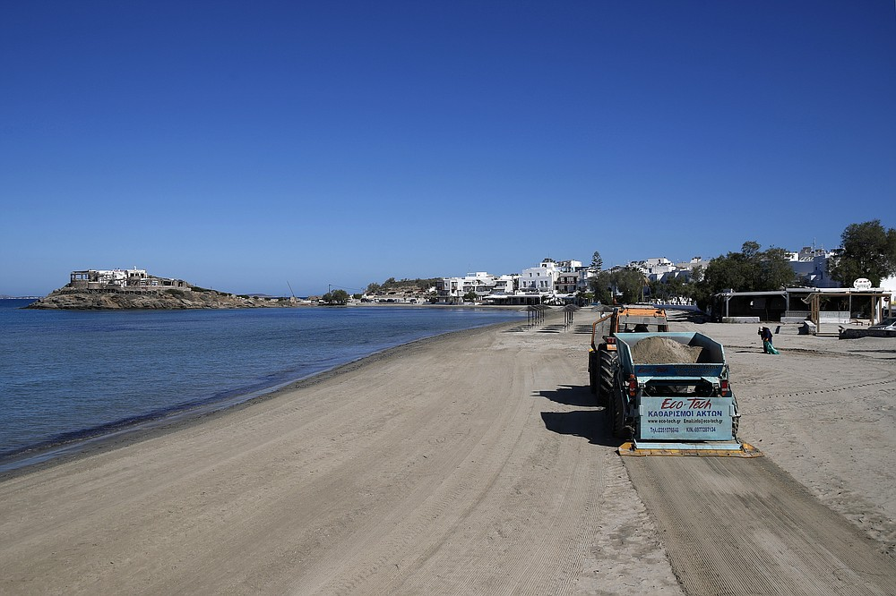 A tractor cleans Agios Georgios beach, on the Aegean island of Naxos, Greece, Wednesday, May 12, 2021. With debts piling up, southern European countries are racing to reopen their tourism services despite delays in rolling out a planned EU-wide travel pass. (AP Photo/Thanassis Stavrakis)