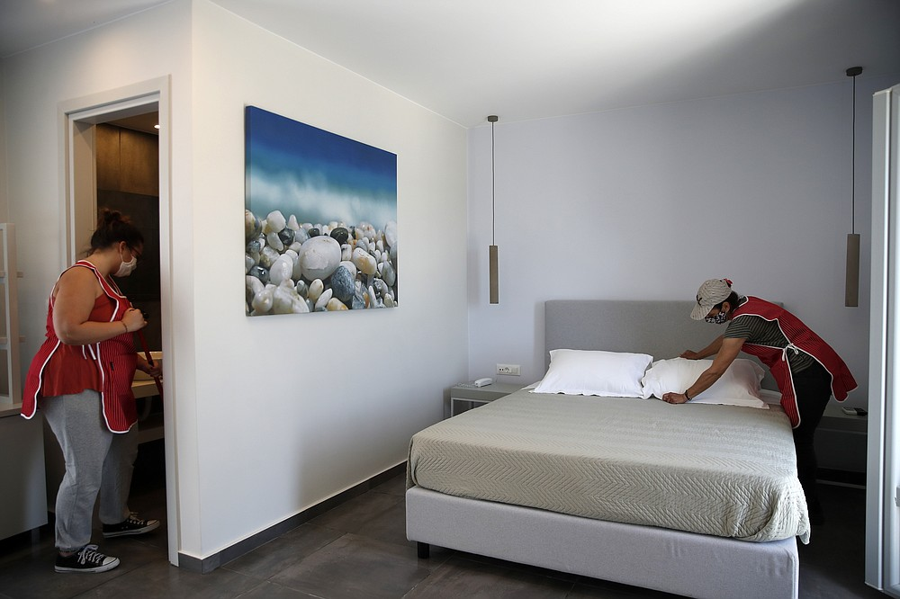 Workers clean a hotel room in Agios Prokopios village, on the Aegean island of Naxos, Greece, Wednesday, May 12, 2021. Greece Friday became the latest country to open up its vacation season as it dismantles lockdown restrictions and focuses its vaccination program on the islands. (AP Photo/Thanassis Stavrakis)