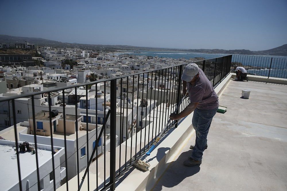 Workers paint the terrace of an all-day cafe bar restaurant in Chora, on the Aegean island of Naxos, Greece, Tuesday, May 11, 2021. (AP Photo/Thanassis Stavrakis)