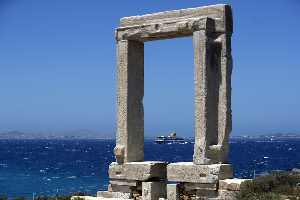 A ferry approaches the port as Portara, a marble gate which is part of an unfinished temple of Apollo of 530 B.C, stands atop of a hill on Aegean island of Naxos, Greece, Tuesday, May 11, 2021. (AP Photo/Thanassis Stavrakis)