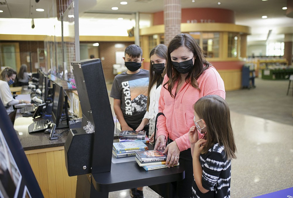 Rowan Herndon, 10, (from left), Amelie Herndon, 13, Katie Herndon and Lucy Herndon, 5, of Bella Vista check out books, Thursday, May 13, 2021 at the Bentonville Library in Bentonville. The Bentonville Library Foundation plans to raise 10.5 million to the full needs assessment plan. Check out nwaonline.com/210514Daily/ for today's photo gallery.  (NWA Democrat-Gazette/Charlie Kaijo)