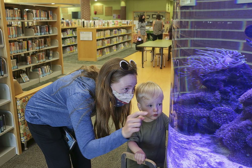 Rachel Burge of Bentonville (from left) and Cody Burge, 2, look into an aquarium, Thursday, May 13, 2021 at the Bentonville Library in Bentonville. The Bentonville Library Foundation plans to raise 10.5 million to the full needs assessment plan. Check out nwaonline.com/210514Daily/ for today's photo gallery.  (NWA Democrat-Gazette/Charlie Kaijo)