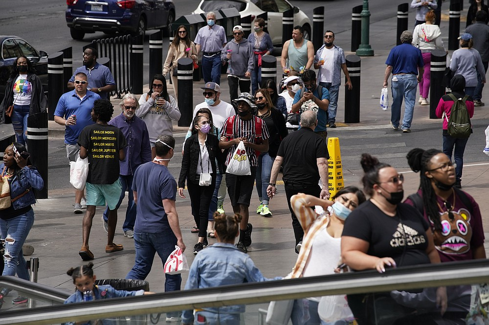 FILE - In this April 27, 2021, file photo, masked and unmasked pedestrians walk along the Las Vegas Strip in Las Vegas. A number of states immediately embraced new guidelines from the CDC that say fully vaccinated people no longer need to wear masks indoors or out in most situations. But other states - and some businesses _ are taking a wait-and-see attitude. (AP Photo/John Locher, File)