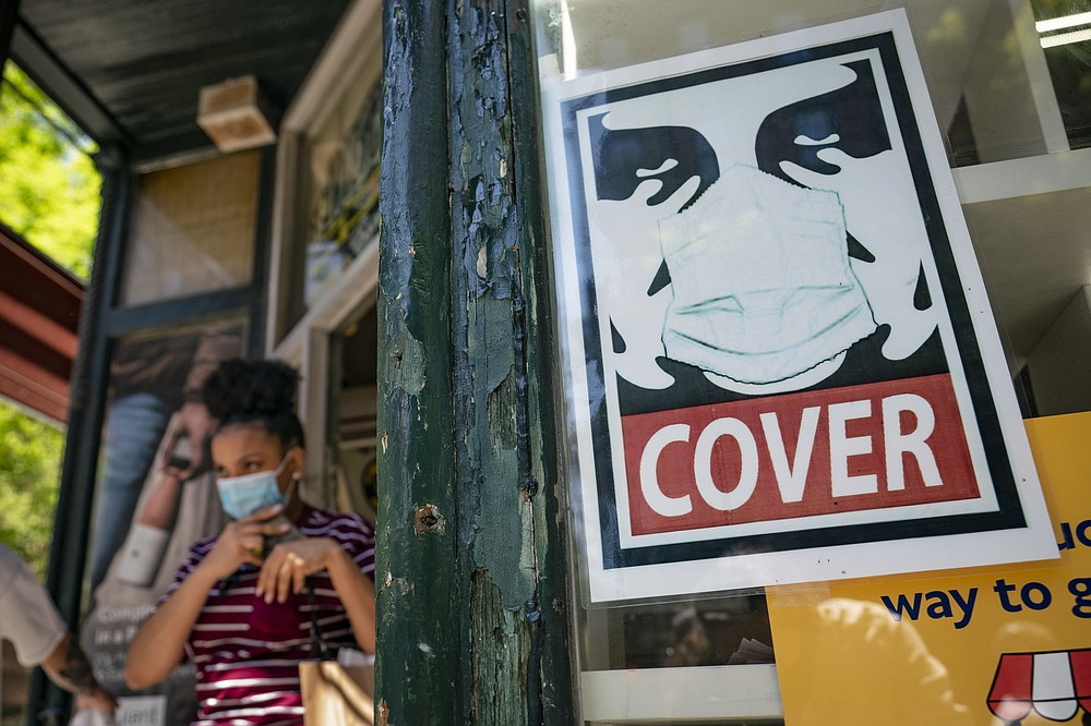 A customer exits a corner market while wearing a protective mask in the retail shopping district of the SoHo neighborhood of the Manhattan borough of New York, Friday, May 14, 2021.  Gov. Andrew Cuomo has yet to say whether he will change his state's mask mandate in light of new federal guidance that eases rules for fully vaccinated people.  (AP Photo/John Minchillo)