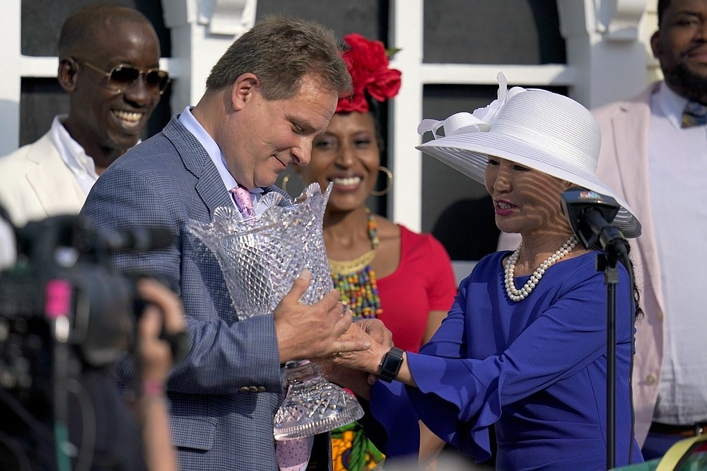 Maryland first lady Yumi Hoagan, right, hands a trophy to trainer Michael Trainer Michael J. Maker after his horse, Army Wife, won the Black-Eyed Susan Stakes horse race at Pimlico Race Course, Friday, May 14, 2021, in Baltimore. (AP Photo/Julio Cortez)