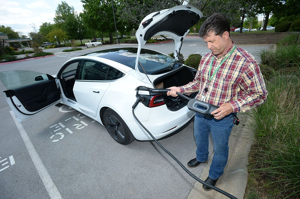 Kris Williams, director of energy services for Ozarks Electric Cooperative Corp. demonstrates how one of the cooperativeÍs Tesla Model 3 electric vehicles is charged Wednesday, May 12, 2021, at the cooperativeÍs offices in Fayetteville. It can be challenging to find charging stations for electric vehicles in rural areas of Arkansas, but both the state and private companies are working to change that. Visit nwaonline.com/210518Daily/ for today's photo gallery.  (NWA Democrat-Gazette/Andy Shupe)