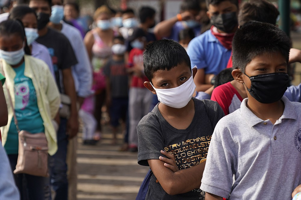 Children and adults wait in lines for donated food at a makeshift camp for migrants near the U.S.-Mexico border Friday, May 14, 2021, in Reynosa, Mexico. Growing numbers of migrant families are making the heart-wrenching decision to separate from their children and send them into the U.S. alone.   (AP Photo/Gregory Bull)