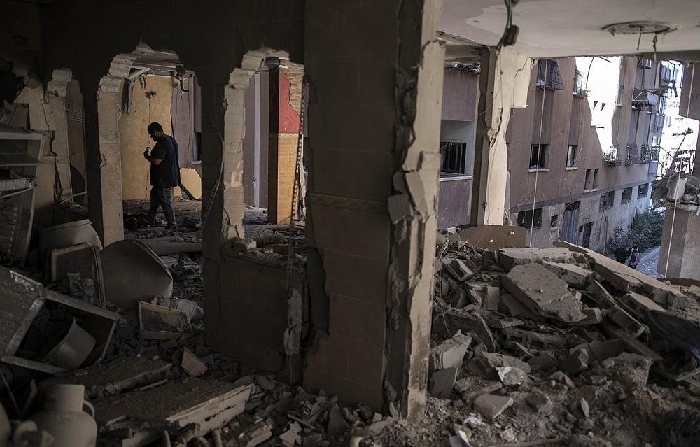 Palestinians look at destruction caused by Israeli air strikes that killed ten members of Abu Hatab Hadidi family in Gaza City, Saturday, May 15, 2021. (AP Photo/Khalil Hamra)