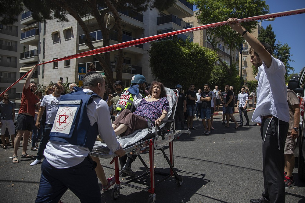 Israeli medics evacuate a woman from a targeted residential neighborhood where a rocket fired from the Gaza Strip hit the area, in Ramat Gan, central Israel, Saturday, May 15, 2021. (AP Photo/Oded Balilty)