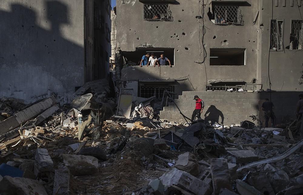 Palestinians look at destruction caused by Israeli air strikes that killed ten members of the Abu Hatab Hadidi family in Gaza City, Saturday, May 15, 2021. (AP Photo/Khalil Hamra)