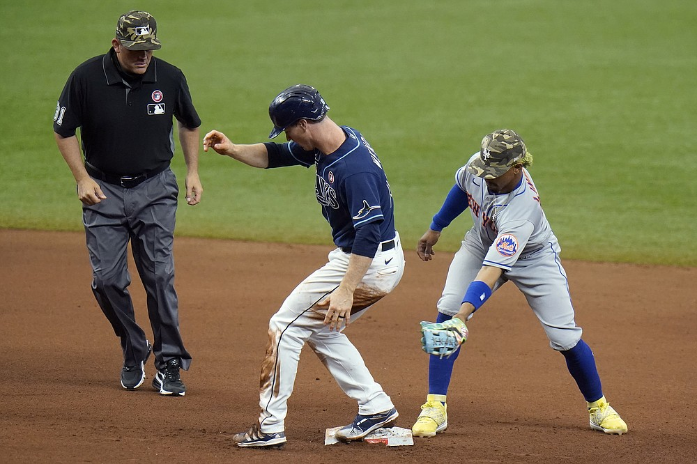 Tampa Bay Rays' Joey Wendle, center reaches second base with a double ahead of the tag by New York Mets shortstop Francisco Lindor, right, during the seventh inning of a baseball game Saturday, May 15, 2021, in St. Petersburg, Fla. Looking on is umpire Brian Knight(AP Photo/Chris O'Meara)